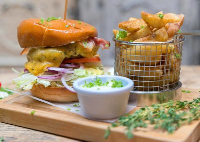 Jerk burger with melted cheese, basket of chips, dipping sauce and colourful garnish at Ruby Tuesday's Soul Food Dublin